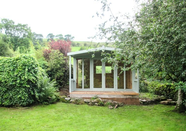 An attractive summerhouse with a chalet-style feel thanks to its overhang and charming veranda. The customer has chosen to have one gable with fully-glazed windows while the other has one large window.