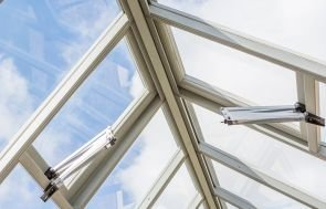 An interior detailed image showing the struts of the automatic opening roof vents inside the greenhouse.