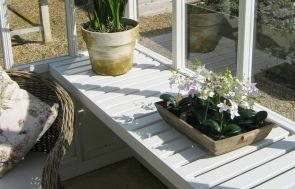 A lifestyle interior image of a greenhouse showing a slatted bench with potting plants on top of it. There is a lounging chair also visible in the image.