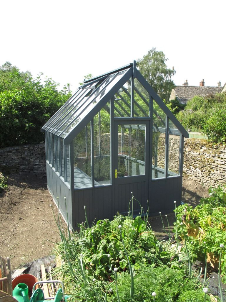 An image showing an attractive, medium sized greenhouse in a walled garden area. The exterior is painted in the exterior shade of Slate.
