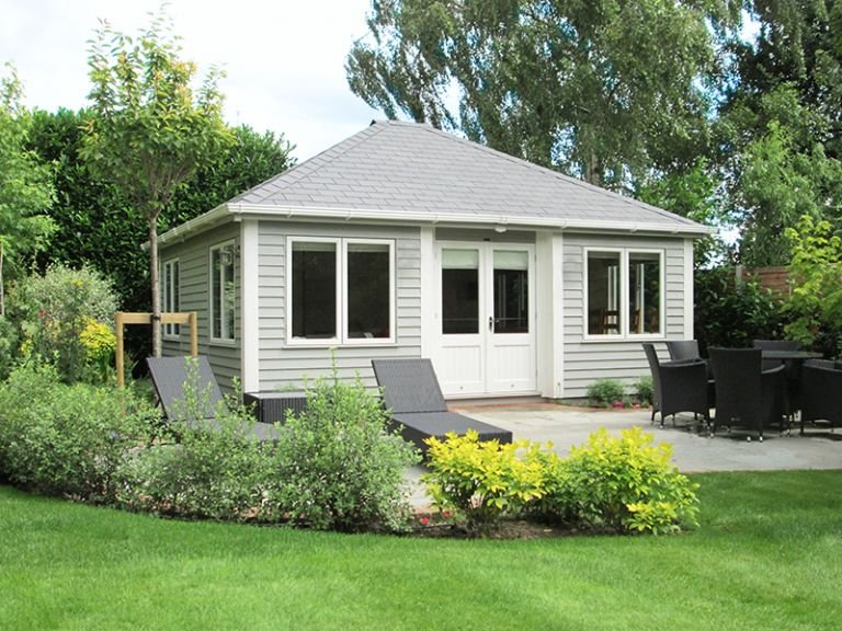 An attractive, large garden room with rustic weatherboard cladding painted in pebble paint. The building has inset doors and corner boards painted in ivory. The hipped roof is covered with grey-slate-composite tiles and all window sets are opening.