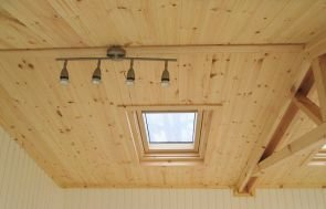 An image showing the interior of an apex roof of a garden room with its truss and velux window as well as the lights that are used in the garden rooms.