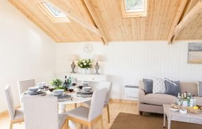 The interior of a garden room with several velux skylight windows and ivory painted walls, decorated with dining table furniture and a sofa with coffee table.