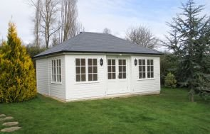 A large garden room in a large garden with large conifers and hedges. The building has a hipped roof covered with grey-slate-composite-tiles and black guttering along the fascia boards. The garden room is clad with smooth shiplap and painted in ivory, with inset doors and corner boards