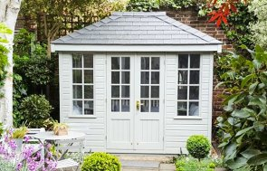 A small cley summerhouse sat in a stunning garden with a variety of shrubbery and flowers. The building is clad with smooth shiplap and has double doors that are half glazed with georgian windows. The building also has windows that feature attractive georgian bars.