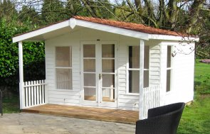 A large Morston summerhouse on a patio area with two chairs visible. The building has a small veranda beneath the overhang of the apex building  and is clad with weatherboard cladding. The roof is covered with cedar shingle tiles and there are several opening windows.