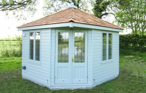 An image of a weybourne summerhouse in a rural spot beneath a tree. The building has a distinctive roof with a slight overhang over the double doors, and is designed to fit into a corner plot. All the windows are leaded and the exterior is clad with smooth shiplap.
