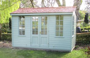 An attractive summerhouse with an apex roof and shiplap cladding. The roof is covered with cedar shingles and the double entrance doors are half glazed with georgian windows. The building is painted in the green shade of lizard.
