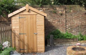 A small classic shed clad with smooth shiplap and painted in light oak preservative stain. It has an apex roof which is covered with heavy-duty, heat-bonded felt.