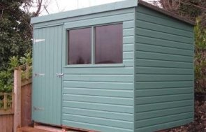 A small classic shed with shiplap cladding and an apex roof covered in heavy-duty felt. The exterior is coated with light oak preservative stain.