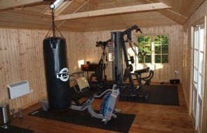 The interior of a large garden room styled as a home-gym with equipment such as a punching bag, free standing weights, a yoga mat and weight machine.