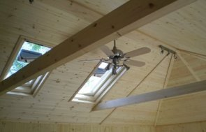 An interior image of a garden room ceiling showing the trusses and a ceiling fan with lights.