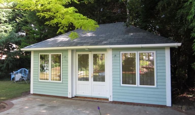A large garden room with inset doors and corner boards painted in a two-tone contrasting style. The building is clad with weatherboard painted in verdigris and has leaded windows with half-glazed doors. Guttering has been added to the fascia boards to keep off the elements.