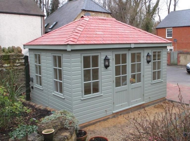 A medium-sized garden room in the colour Sage with Georgian windows and a hipped roof covered in terracotta slate composite tiles