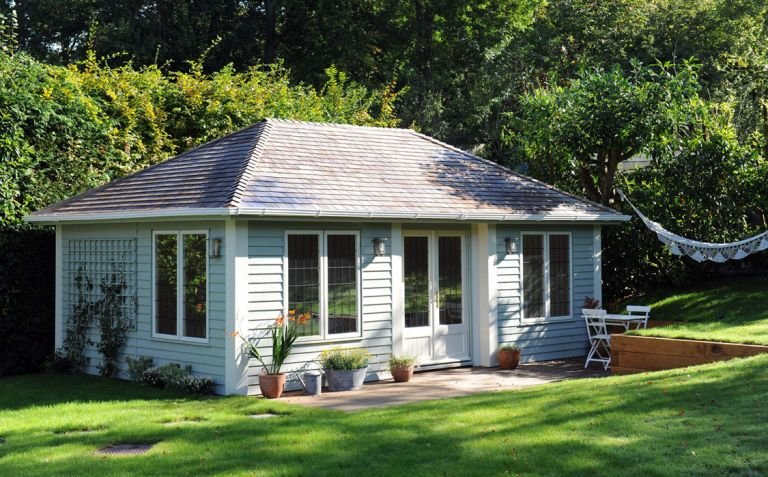 A large garden room building in an attractive garden with a hammock and sunken patio area. The building has a large hipped roof covered with grey-slate-composite tiles and rustic weatherboard cladding painted in verdigris and ivory. The garden room features inset doors and corner boards.