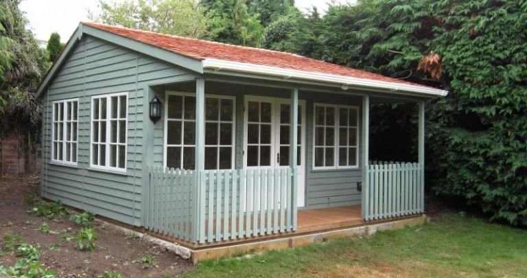 4.8 x 5.4m Garden Room with Veranda with Sage-painted weatherboard cladding, Georgian windows and an apex roof covered in cedar shingle tiles