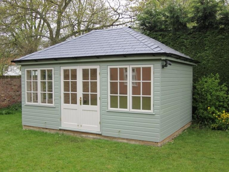 A large garden room with a hipped roof and georgian windows. The exterior is clad with smooth shiplap and painted in the exterior paint shade of sage. Guttering has been added on the fascia boards.
