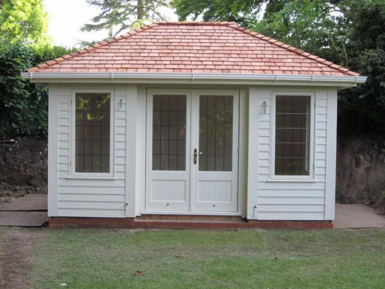 A medium-sized garden building with inset doors and corner boards. Painted in the exterior shade of sandstone, the building is clad with rustic weatherboard and has guttering on the fascia boards.