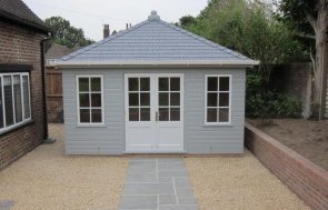 A compact sized garden building with a hipped roof covered with grey-slate-composite-tiles and clad with shiplap painted in the shade of pebble. The doors and windowframes are painted in the contrasting colour of Ivory.