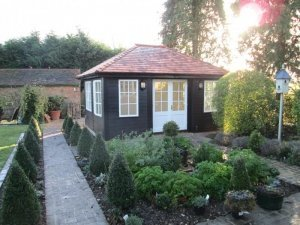 A medium-sized garden room pictured on a patio area with shaped shrubbery. It has a hipped roof covered with cedar shingles and guttering has been added along the fascia boards. The building has weatherboard cladding painted in black and georgian windows painted in ivory.
