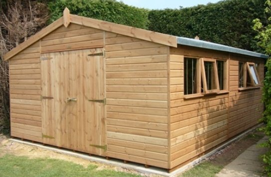 A large superior shed with an apex roof covered in heavy-duty felt. The exterior is clad with smooth shiplap and painted in a light oak preservative which allows the natural beauty of the wood to show through.
