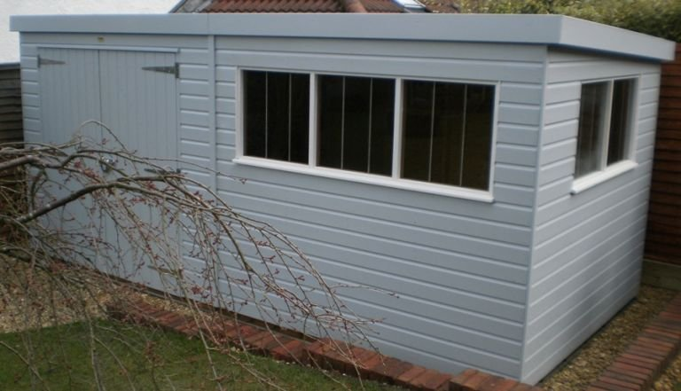 A large garden shed featuring two-tone paint and double door access. Three fixed windows have stainless-steel window bars and the pent roof is covered with heavy-duty felt.