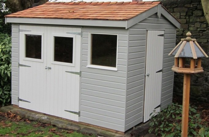 An attractive garden shed with an apex roof covered in cedar shingles. Access is granted via double doors that are painted in ivory, while the rest of the shiplap cladding is painted in pebble.