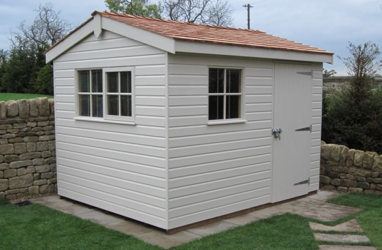 A compact garden shed with an apex roof covered in cedar shingles and shiplap cladding on the exterior. The cladding is painted in both Twine and Ivory in a two-tone fashion.