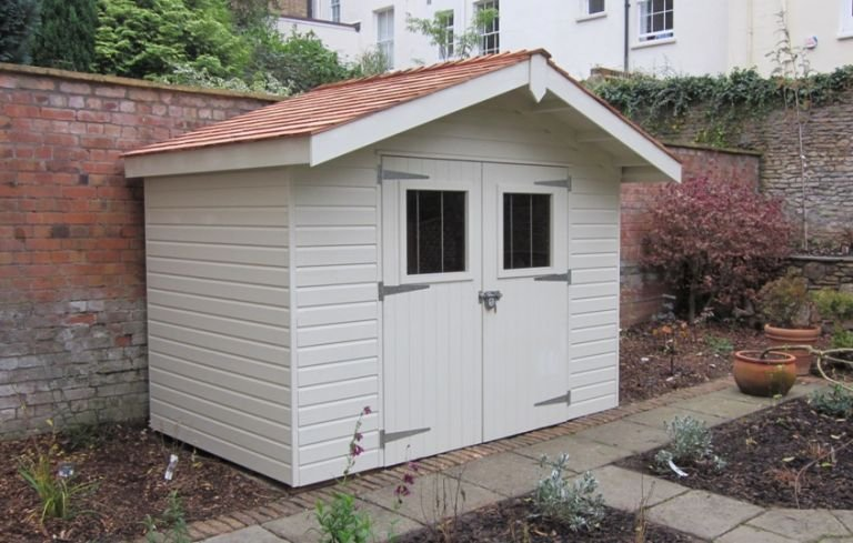 A narrow superior garden shed with an apex roof covered in cedar shingles. Double doors in the gable provide access and a roof overhang provides shelter. A security pack has also been added to the building that features stainless steel window bars and a heavy-duty lock.