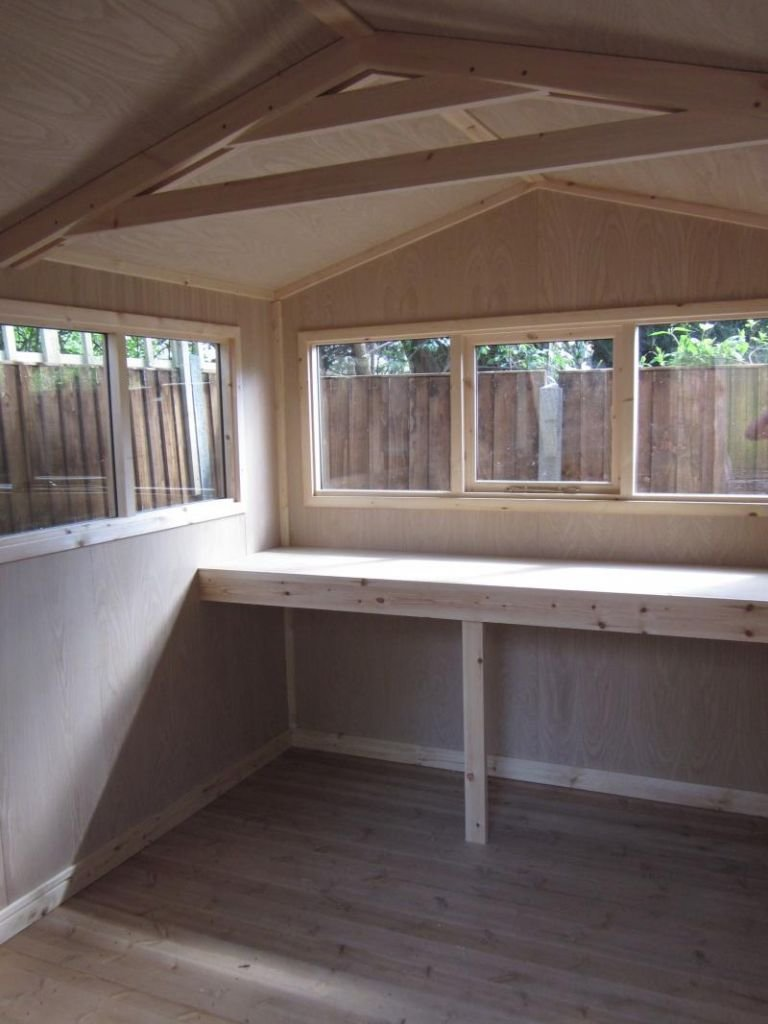 The interior of a lined and insulated superior shed with a workbench beneath three windows. The roof is apex and there is a visible truss supporting the interior of the roof.