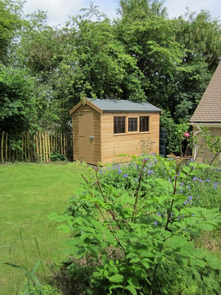 A small superior shed pictured among green surroundings with blue flowers. The shed has an apex roof covered with heavy-duty felt and three windows down the side, which all have stainless-steel window bars. The access door is in the gable of the shed.