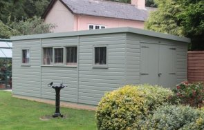 A large superior shed with a sloping pent roof and smooth shiplap cladding. There are double access doors on the gable end and five windows along the side.