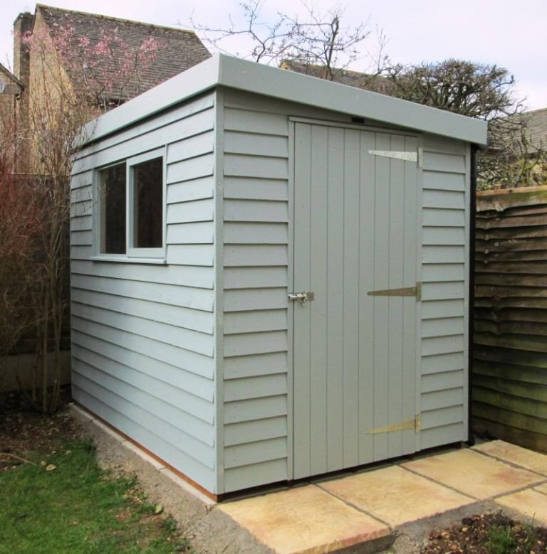 A small superior shed with a single access door and sloping pent roof. The exterior is clad with rustic weatherboard.