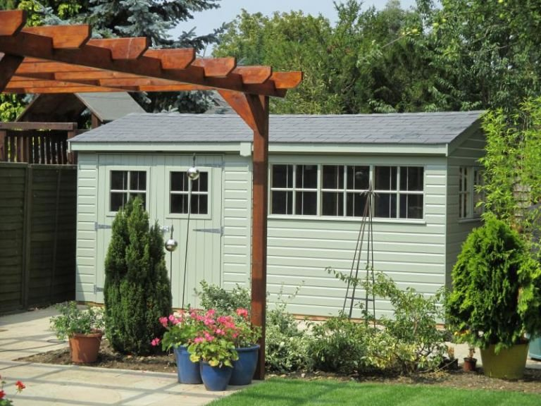 Superior Garden Shed with Double Doors and an apex slate-tiled roof. The shed is in garden surroundings and has attractive georgian windows.