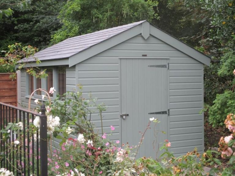 An apex garden shed with slate tiles on the roof and several fixed windows down the side. There is a single access door in the gable and the exterior is clad with smooth shiplap timber painted in Verdigris.