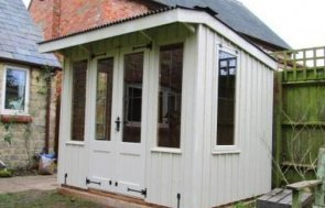 An attractive National Trust summerhouse with a pent roof covered in corrugated material. The building is clad with vertical rustic-cut timber for a traditional look and has leaded windows that open to allow for ventilation.