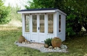 A small attractive national trust summerhouse with a pent roof covered in corrugated material.