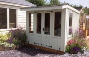 An attractive image of the National Trust flatford summerhouse that has a pent roof and double door access into the interior. It has vertical cladding cut in a rustic, raw way with cast-iron door furniture and leaded windows. The summerhouse is positioned inbetween two vivid flower beds.