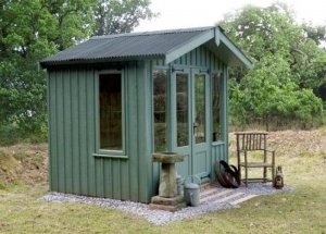 A compact summerhouse with an apex roof and a gable on the overhang. The roof is covered with corrugated sheeting and the exterior of the building is clad with vertically-sawn, rustic-cut timber painted in the terrace green shade of national trust paint.