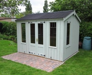 A medium sized national trust Lavenham summerhouse on a small patio area in a grassy garden. The building has an apex roof covered with dark corrugated material and several windows featuring a leaded detail. The cladding is vertically-sawn and rustic cut for a more traditional appearance.