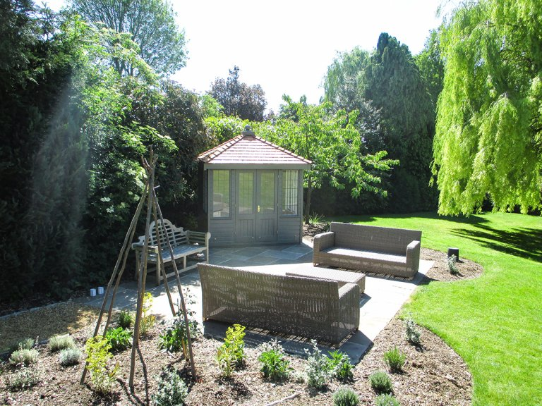 A small, attractive summerhouse pictured in a large garden alongside lounging furniture and with a willow tree in the background. The summerhouse itself has double doors with leaded windows and shiplap cladding painted in the exterior shade of ash.