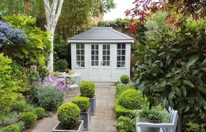 A stunning small summerhouse situated in a beautiful garden with an abundance of shrubbery and colours. The summerhouse has Georgian bars on the windows and a hipped roof covered with slate-composite tiles. The exterior of the building is clad with smooth shiplap and painted in pebble.