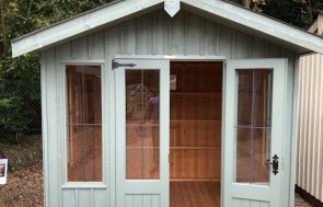 The Ickworth Summerhouse with vertical cladding and an apex roof covered in corrugated material. One of the two double doors is open, showing the natural wood interior and leaded windows.