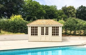 A medium-sized cley summerhouse beside a bright blue swimming pool with smooth shiplap cladding and double doors. The summerhouse has large georgian windows and a hipped roof covered with cedar shingles.