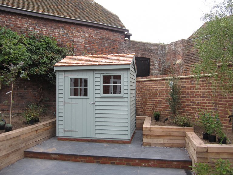 A small, apex shed with a cedar shingle roof and weatherboard cladding. There is a door and single window in the front of the building, both featuring georgian bars.