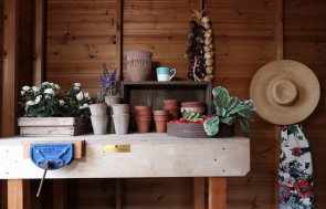 A detailed shot of the inside of a shed featuring a workbench covered in gardening equipment. A sun hat and apron are hung up in the right-hand side of the picture.