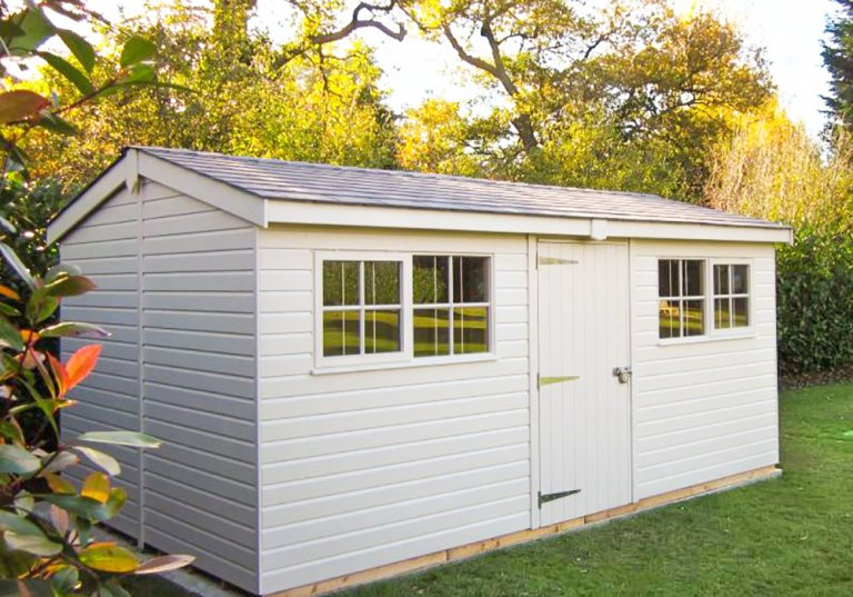 A large garden shed in a well-kept garden with an attractive apex roof covered in grey slate tilers. The exterior is clad with smooth shiplap and painted in our exterior paint shade of pebble.