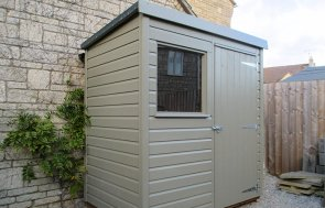 A small classic shed clad with shiplap timber. It has a pent roof covered with heavy-duty, heat-bonded felt and a single fixed window in the front of the building beside a single access door.