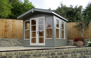 A charming chalet-style summerhouse with an apex roof and slight overhang on the gable. There is double door access into the building and several opening windows for ventilation.