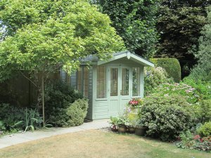 An attractive Blakeney summerhouse with its traditional chalet-style double doors and slight overhang on the apex roof.